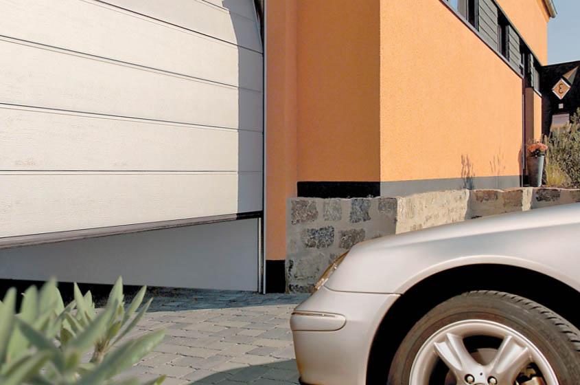Секционные подъемные ворота на въезде в гараж по низкой цене